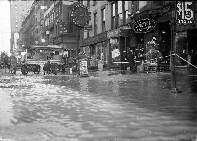 The flood has filled the store cellars with water on Main Street East at Graves Street. All the first floors are submerged as well. A horse and wagon are at the curb and the men are standing on the sidewalk. F.P. Van Hoesen Company, Rienzi (a bar), J.C. Wilson Company, the Postal Telegraph Cable Company, and the Fifth Avenue Clothes Shop are visible in the photo. March, 1913. [IMAGE: Albert R. Stone]