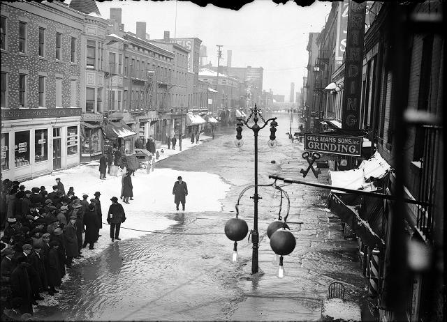 Rochesterians viewing the water on Front Street. Ice has formed in pockets on the flooded street. The sign for Charles Adam's Sons, Inc.,