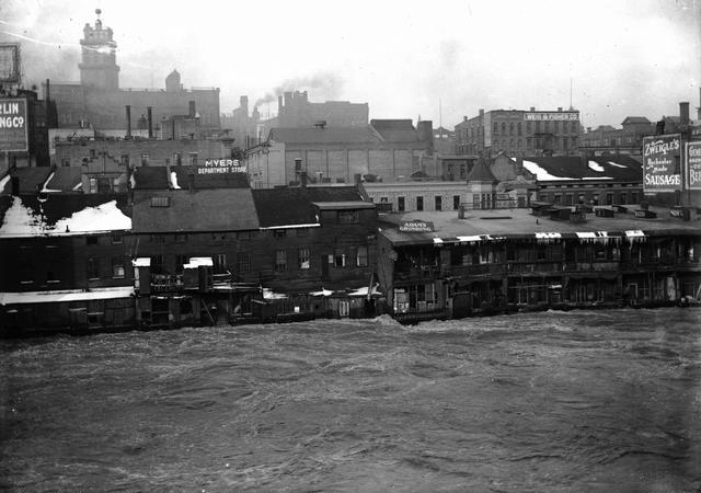 Genesee River in high water stage, showing the backs of Front Street buildings. This is believed to be a depiction of the flood of March 28, 1913. Myer's Department Store, Charles Adam (grinding), and Zweigle's (sausage maker and saloon) are visible in the photo. Weis & Fisher Company (furniture and carpets) is in the right background at 297 Brown Street. The Powers Building tower is in the upper left corner.  March, 1913. [IMAGE: Rochester Municipal Archives]