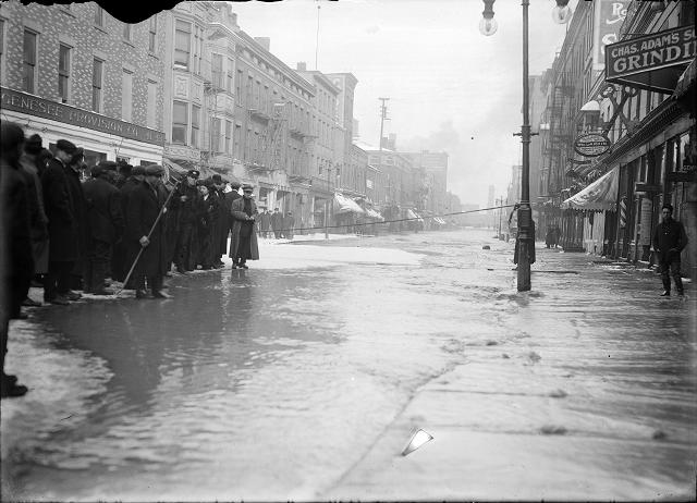 A group of people stand at the edge of the flood water on Front Street in front of the Genesee Provision Company. A rope cordons off the street near Charles Adam's Grinding and the William H. Larkin Hotel. March, 1913. [IMAGE: Albert R. Stone]