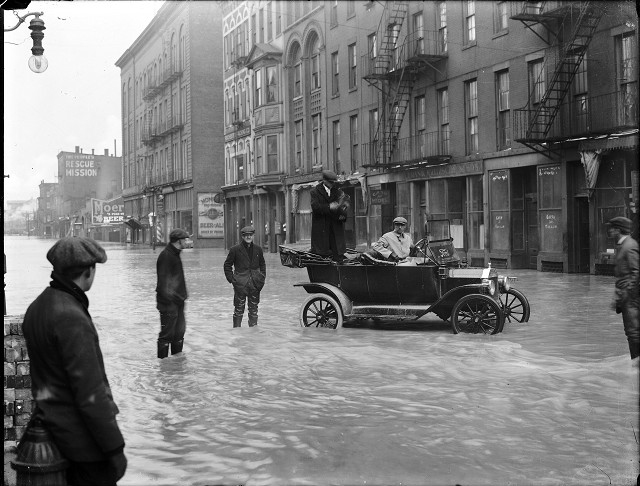 Two men are stopped in a Ford car during the flood on Front Street. One man is holding a camera and other men stand in the street in ankle-deep water. March, 1913. [IMAGE: Albert R. Stone]