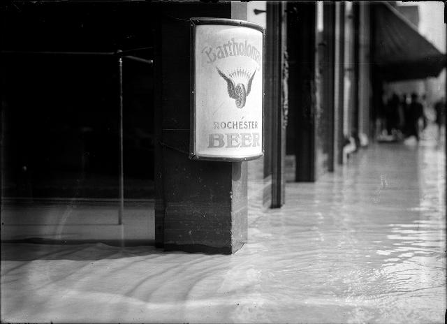 This view is a close-up of flood water going into the shops on Front Street. There is a Bartholomay Beer sign on the post. March, 1913. [IMAGE: Albert R. Stone]