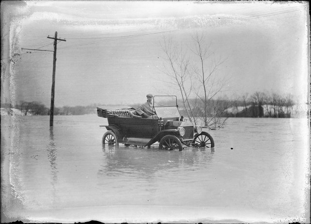 A man sits in a Ford automobile, which has water halfway up the wheels. This is Plymouth Avenue, which has been completely flooded by the Genesee River. March, 1913. [IMAGE: Albert R. Stone]