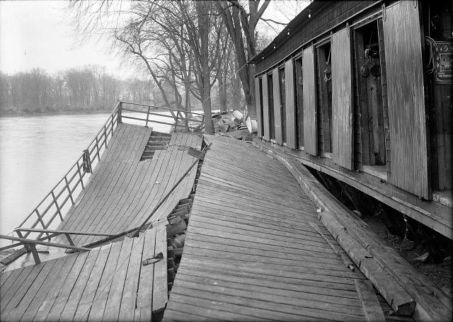 The Durand boathouse in Genesee Valley Park shows major flood damage. The Genesee River, again peaceful, flows past it. March, 1913. [IMAGE: Albert R. Stone]