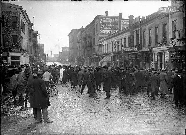People, including one man with a horse and buggy, stand at the edge of the flood on Front Street. Dave Solomon, Pawnbroker and Auctioneer; Charles Adam's Sons, Incorporated, Grinding; Zweigle's; and (probably) the Genesee Provision Company are visible in the photo. March, 1913. [IMAGE: Albert R. Stone]