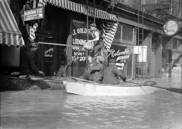Men climb up a ladder from a rowboat to deliver food to families marooned on the upper floors of Rochester's business section. The men are pictured in front of Jacob Goldstein's Lodging House and J.C. Vine's Columbia Hotel. March, 1913. [IMAGE: Albert R. Stone]