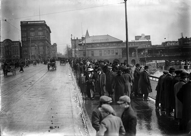 Pedestrians throng the sidewalks of the Court Street Bridge to see the flood waters, as a few horse-driven carriages and automobiles drive past. March, 1913. [IMAGE: Albert R. Stone]