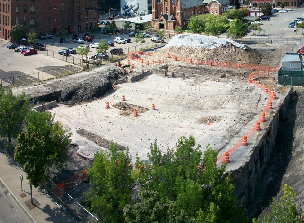 The auditorium floor and stage area of the old RKO Palace are on the left. The open pit on the right is filled with bricks and what appears to be a structural column. Mortimer Street is in the foreground with Saint Paul Street on the far left and Clinton Ave on the far right.