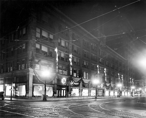 An exterior view of Sibley's as seen at nighttime and decorated for Christmas. 1939. [PHOTO: Rochester Public Library]