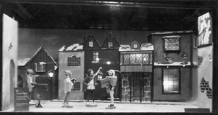 A Sibley's Christmas time window display with the theme of English carolers in a village. 'In Merrie England. The Christmas Carolers on Their Rounds Through the Village. The Spirit of Christmas in is in the air.' 1925. [PHOTO: Rochester Public Library]