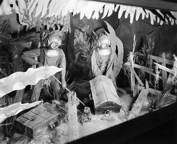 A Sibley's window display showing mannequins in scuba diver gear in an underwater scene with treasure chests. 1940. [PHOTO: Rochester Public Library]