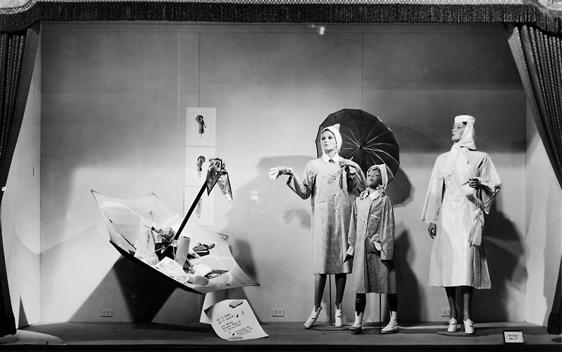 A Sibley's window display featuring mannequins wearing raincoats, pictured with umbrellas. c.1940. [PHOTO: Rochester Public Library]