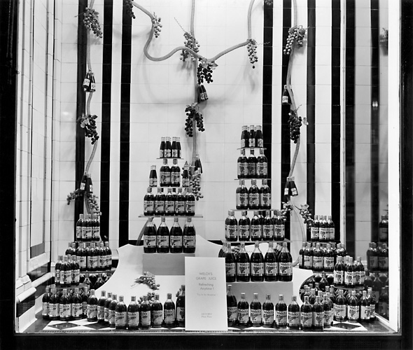 'Welch's Grape Juice. Refreshing Anytime!' A Sibley's window display featuring stacked bottles of Welch's grape juice. 1941. [PHOTO: Rochester Public Library]