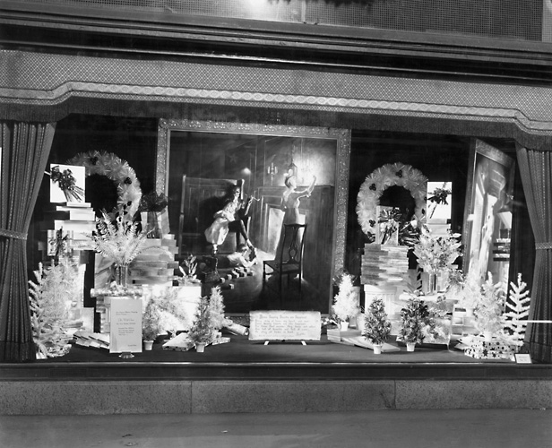 A Sibley's window display at Christmas time showing a variety of wreaths and artificial trees. Also features a copy of an oil painting by William L. Taylor based on a poem by Henry Wadsworth Longfellow, 'Home Keeping Hearts are Happiest.' 1940. [PHOTO: Rochester Public Library]