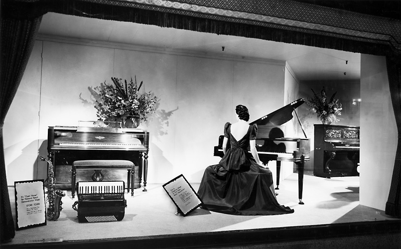 A Sibleyd's department store window display featuring a mannequin seated at a piano, a second piano, a saxophone and an accordion. (1940). [IMAGE: Rochester Public Library]