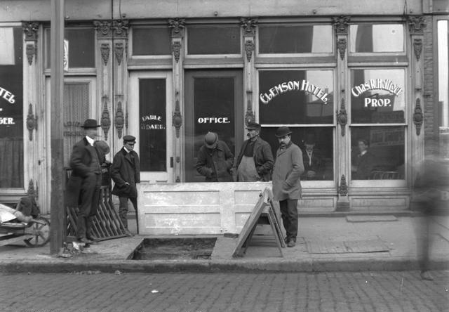 These men are standing around a hole in the sidewalk where John Hornby and James Kenney fell through on December 11, 1901. In the background is the Clemson Hotel, with Charles R. Holliger, proprietor, at 52 South Avenue. [PHOTO: Rochester Municipal Archives]