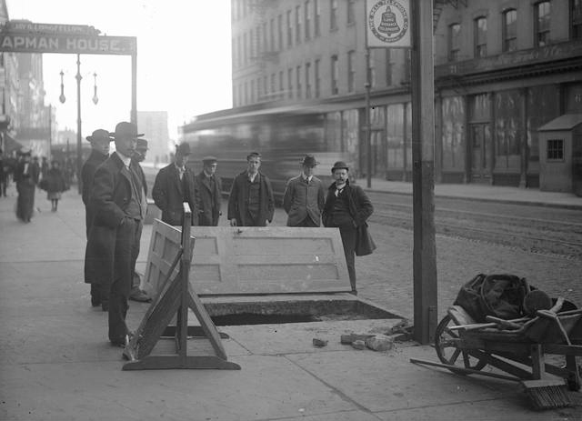 Looking south on South Avenue from just south of Ely Street. To the left is a sign for the Chapman House which was at 62 South Avenue, with Jay G. Longfellow as proprietor. Men are standing around a hole in the sidewalk where John Hornby and James Kenney fell through. A streetcar can be seen behind the men, and a wheelbarrow full of tools is in the foreground. A sign for Bell Telephone Company of Buffalo is on the post. [PHOTO: Rochester Municipal Archives]