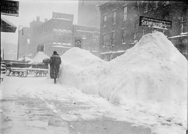 People walk along the snowy sidewalk on North Water Street after a snowstorm. This storm was 1914 (not the 1900 storm that Jim's Grandfather battled). The piles of snow between the sidewalk and the road are higher than people's heads. Sleds and wagons on sled runners are parked on the sidewalk. Visible business signs include Brewster, Gordon & Co., grocers, 39 North Water Street; Robertson & Sons, shoemakers, 38 North Water Street; Morrison Press, book and job printing, 60 North Water Street. [PHOTO: Rochester Municipal Archives]