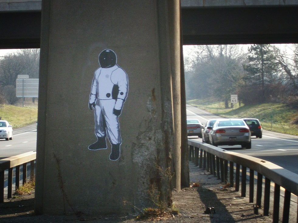 This Spaceman is stuck to a railroad bridge support column on I-490. He is facing eastbound traffic.