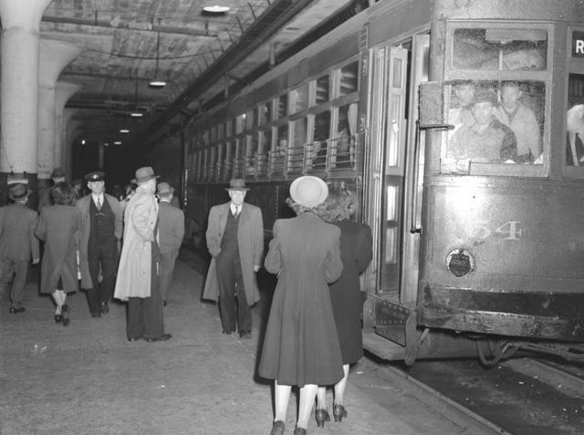 A bustling subway station scene, showing people crowding the platform, and passengers lining up to leave the subway car. The scene is the underground City Hall station located at Broad and Exchange Streets. The eastbound car is heading for the end of the line at Rowlands. [Image from Rochester Municipal Archives]