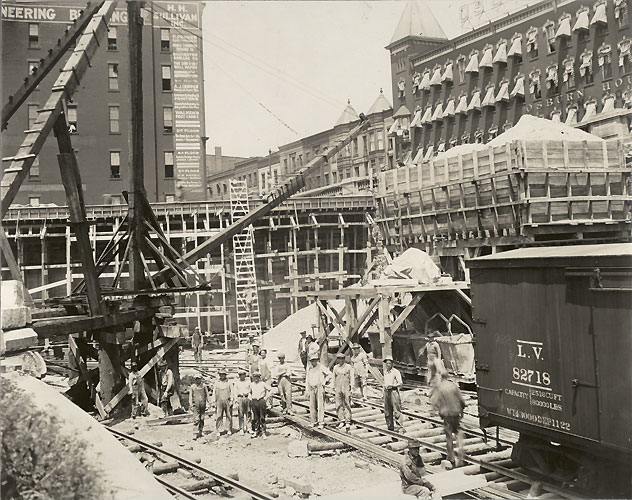 Well-dressed men line up to climb a wooden ladder out of an excavation. The large area, bordered by steep stone walls, is part of the subway excavation. [Image from Albert R. Stone collection]