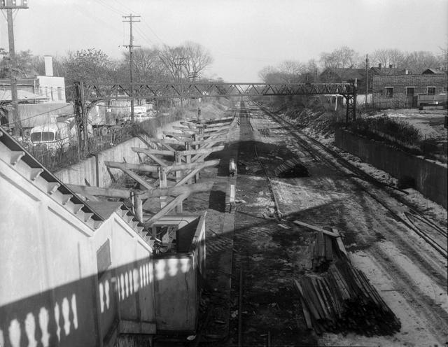 A view looking east along the Rochester Subway bed from the Monroe Avenue bridge, showing the stairway leading from the bridge to the Monroe Avenue subway station. The station has been partially dismantled, in preparation for the construction of Interstate 490 in the subway bed. [Image from Rochester Municipal Archives]