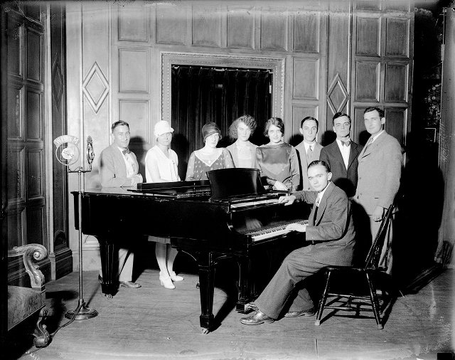 This group is gathered around a piano to perform for a WHAM radio broadcast (c.1927). The microphone is at far left. Identified are: 4th from left, Florence Knope Freeman; far right, Clayton Knope; at piano, James Quillian. [IMAGE: Albert R. Stone Negative Collection]
