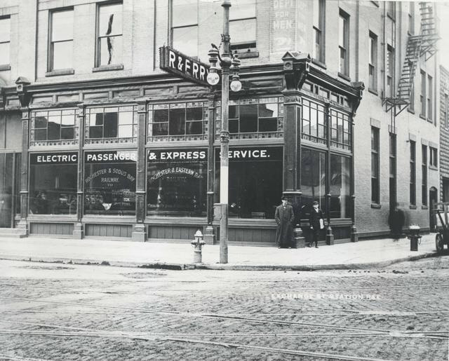 The Exchange Street station for interurban railroads at 112 Exchange St. (northeast corner of Court and Exchange). The station was used by the Rochester and Eastern Rapid Railway and the Rochester and Sodus Bay Railway until 1927. People are standing on the corner. The sign on the window reads Electric Passenger & Express Service. The building was razed in 1951 to make way for the War Memorial.