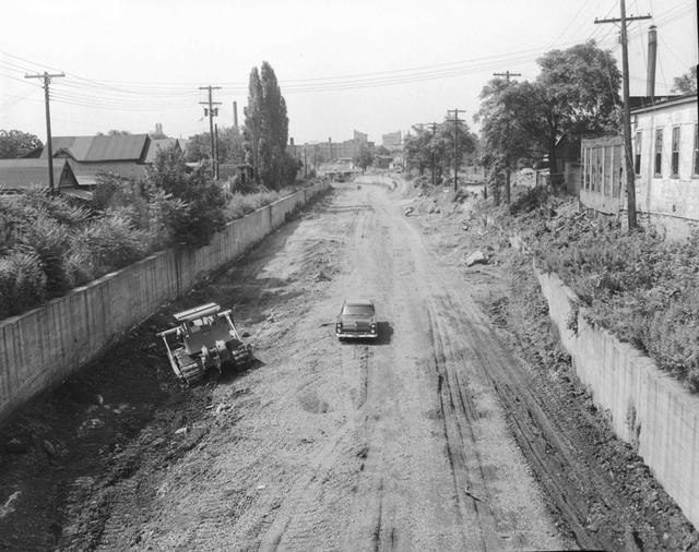 Construction of Interstate 490 in the Rochester subway bed along the former route of the Erie Canal. A bulldozer with a brush rake is doing the initial clearing of the site. The view is looking west from the Averill/Alexander Street area. July 1956.