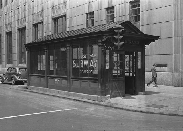 Entrance to the City Hall subway station. This kiosk is on Broad Street at the northwest corner of Exchange Street, with the Times Square building in the background. A man in a summer hat is seen walking on the sidewalk.