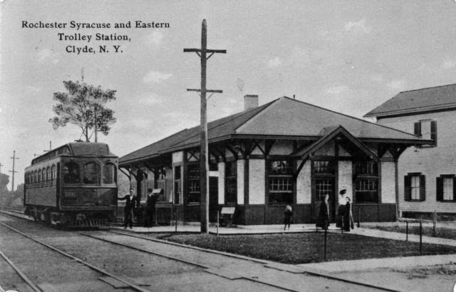 A view of the Rochester, Syracuse and Eastern interurban trolley station in Clyde NY. A street car, tracks and people are seen. This station was built between 1906 and 1911, and was a stopping point between Rochester and Syracuse.