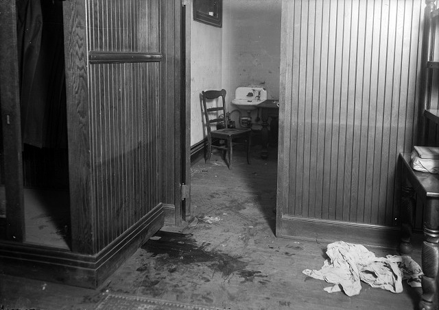 A large pool of blood marks the spot where J. Frank 'Scrappy' O'Connor bled to death. A pile of rags lies on the floor nearby. In the background is the room with a sink where the assailant washed his hands, stepping over O'Connor's body in order to do so. [PHOTO: Albert R. Stone Collection]