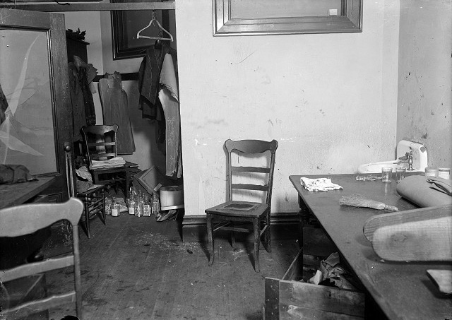The floor of the closet in J. Frank O'Connor's tailor shop is full of gin bottles. Clothing under construction hangs in the closet. Several straight chairs stand around the room. The glass in the door to the room has been shattered. In the far right corner, beyond the table with a bolt of cloth, a pressing board, and a whisk broom, is the sink where the murderer supposedly washed his hands. [PHOTO: Albert R. Stone Collection]