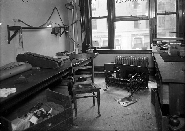 This was the Sibley Building office, and murder scene, of J. Frank O'Connor, a tailor merchant. A sewing machine and its table have been knocked over and lie in front of the radiator. The cutting table is at the right. A lower table, on the left, holds a bolt of fabric, a pressing board for sleeves, and an electric iron. A chair and a box of material sit in front of the lower table. [PHOTO: Albert R. Stone Collection]