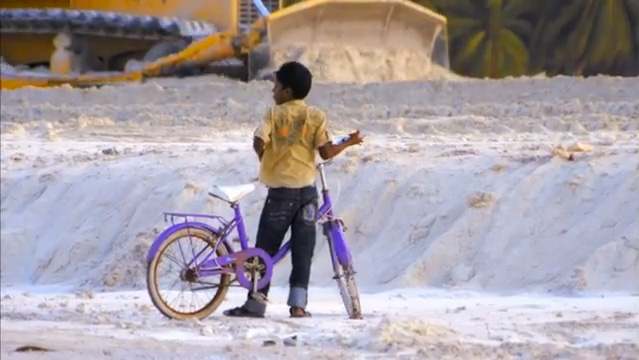 Boy watches as industrial equipment is used in an attempt to shore up his homeland.