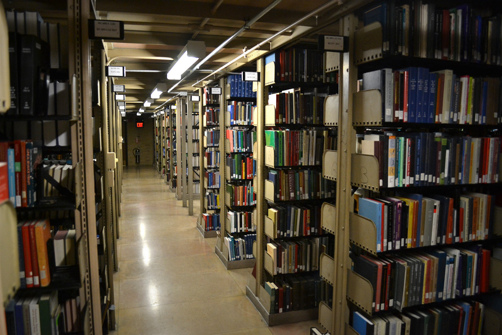 Shelves of books in a dimly lit level of the library
