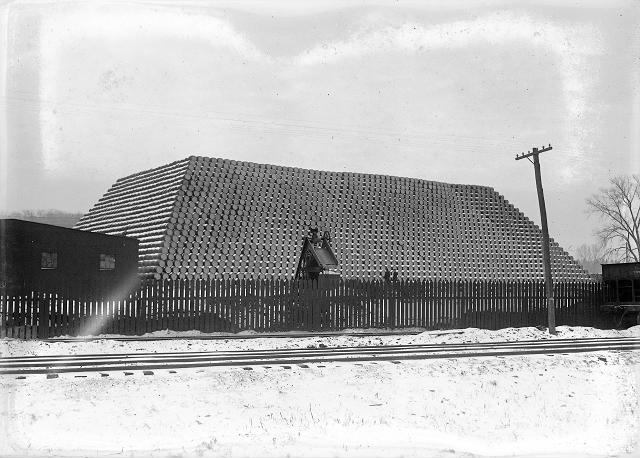 57,000 oil barrels are neatly stacked off Plymouth Avenue South, near the tracks of the Pennsylvania and Erie Railroads. The barrels are at the Rochester plant of the Vacuum Oil Company. February 24, 1918. [IMAGE: From the Albert R. Stone Negative Collection, Rochester Museum & Science Center, Rochester, NY.]