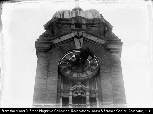 A repairman works on the Sibley Building clock tower [PHOTO: Albert R. Stone Negative Collection, Rochester Museum & Science Center]